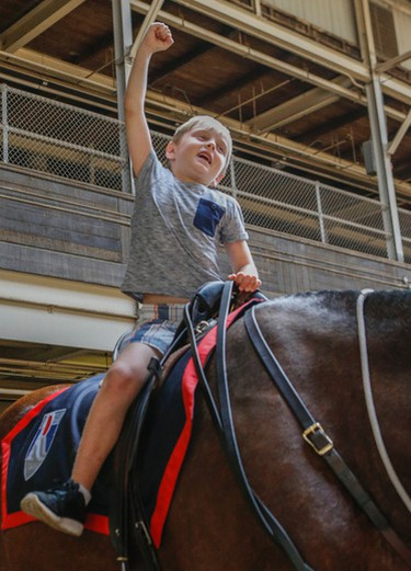 Nolan Russell, 7, son of slain Toronto Police Sgt. Ryan Russell, takes a ride on the  four-year-old Purebred Clydesdale named Russell for his father at the Toronto Police Services Mounted Horse Palace Tuesday, June 21, 2016. (Dave Thomas/Toronto Sun)