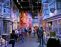 In this May 23, 2015 photo, tourists stroll along the Diagon Alley movie set at The Making of Harry Potter Warner Bros. Studios experience in London. Visitors can view props, costumes and sets, including Platform 9 ¾, the Night Bus, Harry's cubbyhole at Number 4 Privet Drive and a miniature Hogwarts campus. You can get filmed riding your very own Nimbus 2000, or pile the family into the Weasley invisible car for a group photo. (AP Photo/Ross D. Franklin)