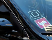 In this Tuesday, Jan. 12, 2016, file photo, a driver displaying Lyft and Uber stickers on his front windshield drops off a customer in downtown Los Angeles. (AP Photo/Richard Vogel, File)