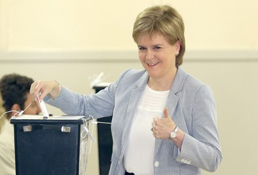 Scotland's First Minister, Nicola Sturgeon, casts her vote in Glasgow, Scotland, Thursday, June 23, 2016, as voters head to the polls across the United Kingdom in a historic referendum on whether the U.K. should remain a member of the European Union or leave. (Jane Barlow/PA via AP)