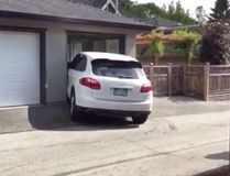 A white Porsche Cayenne SUV is seen struggling to get into a parking spot. (YouTube screenshot)