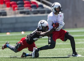 Ottawa Redblacks wide receiver Chris Williams makes a catch as defensive back Jerrell Gavins makes the tackle during practice at TD Place in Ottawa on June 21, 2016. (Errol McGihon/Postmedia)