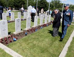 Emily Mountney-Lessard/The Intelligencer 8 Wing base commander Col. Colin Keiver looks at graves in the Commonwealth War Graves section of the St. following the rededication of a monument recognizing the British Commonwealth Air Training Plan on Friday.