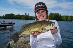 Author Ashley Rae with a largemouth bass caught on opening day of bass season with some nearby boaters cheering her on.