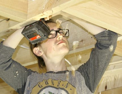 Keegan McNeight drills holes for electrical lines in a bunkie being constructed by the Technical Training Group Pre-Apprenticeship Multiple Trades Program at St. Michael Catholic Secondary School on Monday. STEVE RICE/The Beacon Herald