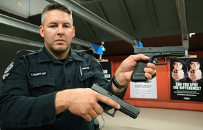 Edmonton Police Service (EPS) Constable Clay Hilbert (Firearms Training Unit) holds two handguns, one real, the other a fake. EPS launched a safety campaign in Edmonton on Wednesday June 29, 2016.