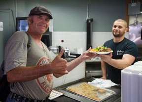 George, shows his pleasure as he's handed a meal by Shelby's Food Express owner Yazan El-Shalabi. The restaurant, which recently was sending proceeds to Fort McMurray fire victims has now teamed app with the Salvation Army and the London Muslim community to host a free meal for 200 people who live in shelters in London. (MIKE HENSEN, The London Free Press)
