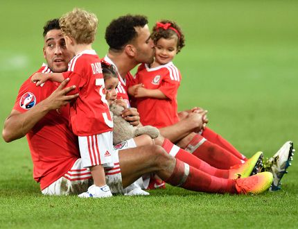 Wales' James Chester, left, and Hal Robson-Kanu play with their children on the pitch at the end of the Euro 2016 quarterfinal against Belgium at the Pierre Mauroy stadium in Villeneuve d'Ascq, near Lille, France, Friday, July 1, 2016. (AP Photo/Martin Meissner)