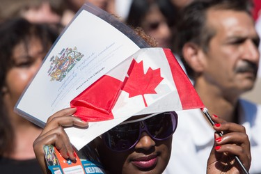 EDMONTON ALBERTA: July 1, 2016 Helen Chiquaqo shades herself from the sun with the Canadian flag and her certificate after being sworn in as a new citizen during Canada Day festivities at the Alberta Legislature in Edmonton July 1, 2016. AMBER BRACKEN/EDMONTON JOURNAL