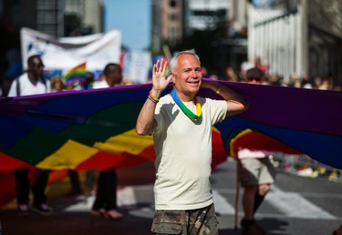A man waves while carrying a rainbow flag at Toronto's Pride parade held in downtown Toronto, Ont.   on Sunday July 3, 2016. Ernest Doroszuk/Toronto Sun/Postmedia Network