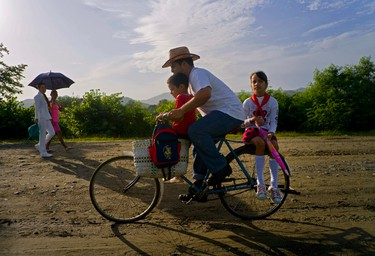 In this June 15, 2016 photo, Yosbani Rodriguez bikes his son Meiler and daughter Mayla to school before work in Biran, Cuba. Rodriguez works as the historian at the nearby home-turned-museum where Fidel Castro and his brother, President Raul Castro, grew up. (AP Photo/Ramon Espinosa)