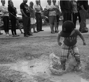 On Canada Day, my son Grayson, 2, splashes in a puddle while the locals wait in line at the annual Seaforth Firefighters' Breakfast.(Shaun Gregory/Huron Expositor)