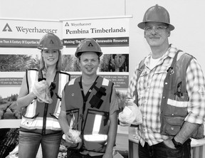 Weyerhaeuser representatives (l. to r.) summer student Kc Rhoades, summer student Chris Sopuch and Operation Planner Bill Taylor were busy handing out tree seedlings at the ECDC open house held June 22. They are now in the process of counting pine beetles in the area.