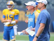 Winnipeg Blue Bombers offensive coordinator Paul LaPolice (l) and head coach Mike O'Shea watch play during CFL football practice in Winnipeg, Man. Tuesday July 05, 2016.