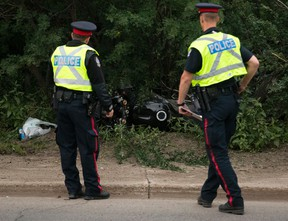 Police investigate at the scene of a fatal motorcycle crash along Bellamy Hill near 99 Avenue, in Edmonton on Tuesday July 5, 2016.