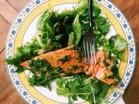 This May 13, 2016 photos a fillet of salmon smothered in an herb marinade served over a tender green salad, in New Milford, Conn. This warm-weather recipe combines salmon bathed in olive oil and herbs with spring-y greens and salad. It's the kind of lighter, brighter meal we tend to want during summer.