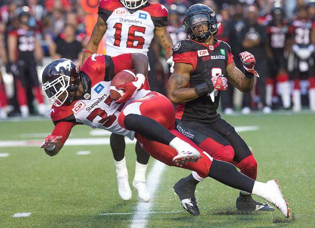 Calgary Stampeders running back Jerome Messam tries to squeeze past Jermaine Robinson of the Redblacks during the home opener at TD Place. (Wayne Cuddington, Postmedia Network)