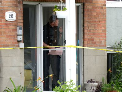 An Ottawa Police officer looks out from inside a home at the scene of an overnight homicide in Lowertown in Ottawa on Sunday, July 10, 2016. Justin Tang