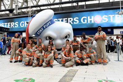 LONDON, ENGLAND - JULY 11:  Fans pose with Stay Puft Marshmallow Man on the concourse at Waterloo Station on July 11, 2016 in London, England. Ghostbusters take over Waterloo Station as Stay Puft Marshmallow Man smashes through the concourse during the morning rush-hour. Standing at 2.9m in height with a circumference of 8.5m commuters come face-to-face with the mammoth menace. Ghostbusters is in cinemas from today  (Photo by Gareth Cattermole/Getty Images for Sony Pictures)
