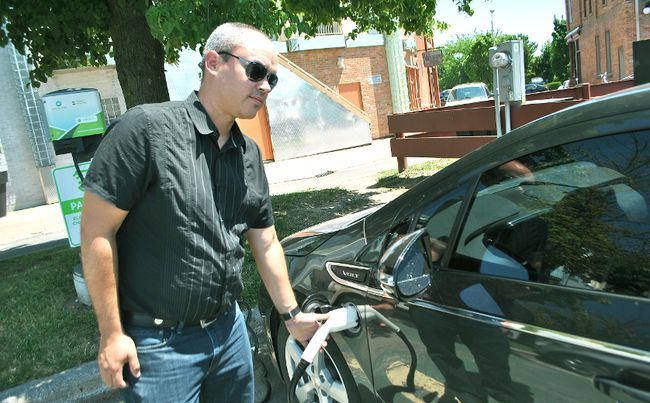 Tom Morrison/The Daily News Sean Hart plugs in his friend's Chevrolet Volt at the electric vehicle charger at the Downtown Chatham Centre Wednesday. The province has announced an additional three chargers for Chatham-Kent.