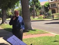 "John Williams greets two young musicians after they successfully play the ""Star Wars theme outside of the famous composer's home. (YouTube)"