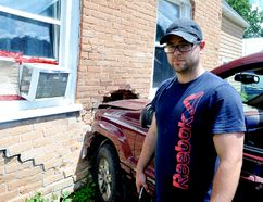 Luke Donaghy points to the damage caused to his home when a Jeep Grand Cherokee ran into it shortly before noon on Sunday. (RONALD ZAJAC/The Recorder and Times)