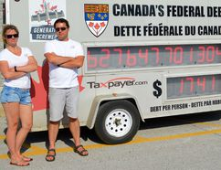 Ontario director Christine Van Geyn and federal director Aaron Wudrick of the Canadian Taxpayers Federation stand beside the Federation's debt clock, during a recent visit to Petrolia. Melissa Schilz/Postmedia Network