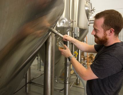 Gavin Anderson of Anderson Craft Ales taps a sample of his first brew at their Elias Street location in London. (MIKE HENSEN, The London Free Press)