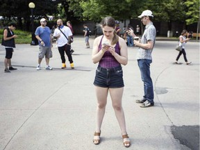 Leanne Sharzer, centre, was one of a few hundred people gathered for a Pokemon Go Lure Party in Confederation Park Tuesday, July 19, 2016. Darren Brown/Postmedia