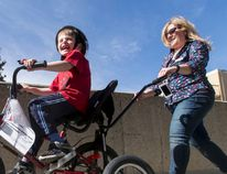Jeremiah Botbijl, 6, is thrilled atop a customized bicycle while being followed by Sheralee Stelter, executive director of Cerebral Palsy Kids and Families, at the group's headquarters in Calgary on Saturday, April 2. About 35 kids with physical disabilities like cerebral palsy, down syndrome and autism were fitted with customized bicycles; the group expects to give out 200 bikes this year but could do more if supplies were available. Lyle Aspinall, Postmedia Network.