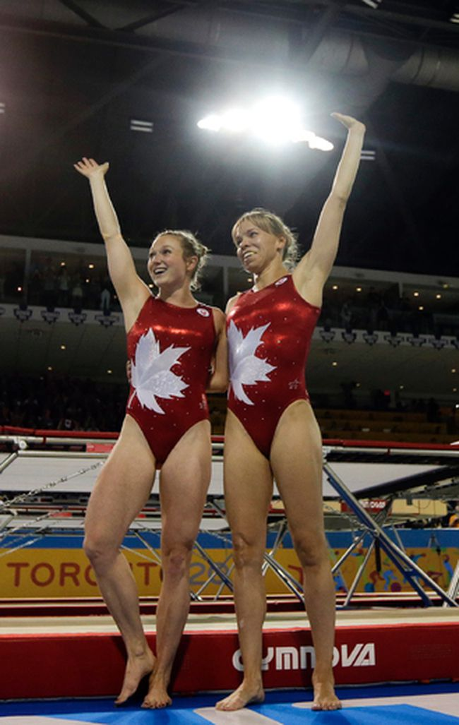 Canada's Rosie MacLennan (left) and Karen Cockburn (right) wave to the crowd during the women's trampoline competition at the Pan Am Games in Toronto on July 19, 2015. MacLennan will defend her Olympic gold medal at the Rio Olympic Games next month. (Gregory Bull/AP Photo/Files)