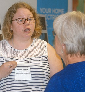 Otter Creek Wind Farm's Alexandra Agagnier talks with Kris Lee during a public meeting regarding the proposed wind farm for north of Wallaceburg. David Gough/Postmedia Network