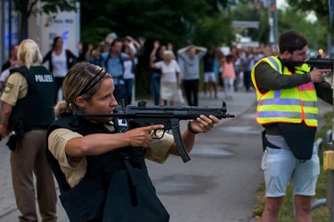 Police officers guard with guns as they escort people near from inside the shopping center as they respond to a shooting at the Olympia Einkaufzentrum (OEZ) at July 22, 2016 in Munich, Germany.   (Photo by Joerg Koch/Getty Images)