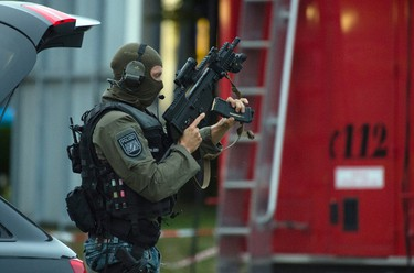 Police officer search a residential area near the Olympia shopping centre after a shooting was reported there in Munich, southern Germany, Friday, July 22, 2016.  (Matthias Balk/dpa via AP)