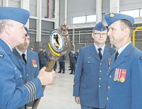 Incoming Commanding Officer Lt. Col. Todd Murphy accepts the 8 Air Maintenance Squadron Mace from 8 Wing Commander, Col. Colin Keiver during a Change of Command ceremony Friday. They are joined by outgoing Commanding Officer Lt. Col. Andrew Wedgwood and Squadron Chief Warrant Officer Daniel Murphy.