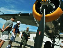 "Tom Morrison/The Daily News John Koekuyt, second from left, speaks with Rex Kanitz, right, underneath the wing of a Yankee Warrio B-25D ""Mitchell"" Bomber during the Chatham-Kent Flight Fest at the Chatham-Kent Municipal Airport on Saturday."