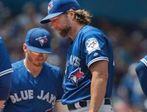Blue Jays starting pitcher R.A. Dickey waits on the mound for manager John Gibbons in the fourth inning against the Mariners during MLB action in Toronto on Saturday, July 23, 2016. (Fred Thornhill/The Canadian Press)