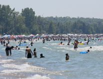 People at the beach Saturday afternoon said a man died after he got into trouble in the water at the south end of Sauble Beach. Thousands of bathers crowd the warm waters of Lake Huron to beat the heat on Saturday at Sauble Beach. (James Masters/The Owen Sound Sun Times/Postmedia Network)