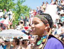 <p>A dancer smiles as she enters into the exhibition area during the Grand River Champion of Champions Powwow at Six Nations' Chiefswood Park on July 23.