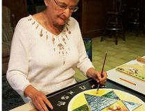 Nora Ann Harrison in her home studio with Symbolic Elements, an encaustic, ink and acrylic piece she created several years ago.