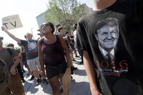 A Black Lives Matter protester shouts slogans next to next to a supporter of Republican presidential candidate Donald Trump, right, in Public Square on Tuesday, July 19, 2016, in Cleveland, during the second day of the Republican convention. (AP Photo/Mary Altaffer)