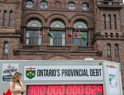 Christine Van Geyn, Ontario director of Canadian Taxpayers Federation, looks on as the provincial debt clock turns over the $300 billion mark at Queen's Park in Toronto on Monday, July 25, 2016. (Dave Thomas/Toronto Sun)