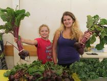 Beet lovers, rejoice! Alexa Graham,13, left, and her 17-year-old sister Sarah held up some of the giant vegetables that were available for purchase at the kick-off to the annual Mountjoy Independent Farmer's Market on Saturday afternoon at the Centennial Hall.