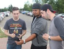 Bryce Way, from left, Jean-Marc Giroux and Bryce Talarico talk Pokemon Go while in Muskoseepi Park on Sunday. The trio individually run three of the local team Facebook pages Team Yellow: Instinct (Way), Team Blue: Mystic (Giroux), and Team Red: Valor (Talarico). Jocelyn Turner/Daily Herald-Tribune