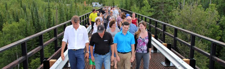 Riversedge Developments CEO Justus Veldman, front left, leads the first crossing of the Abitibi Bridge after its official grand reopening on Wednesday afternoon. The bridge surface is a grate that allows walkers to see the Abitibi River below.