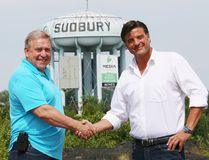 Gates Perreault, left, of the Adaptive Canuck ALS Foundation, shakes hands with Dario Zulich, CEO of TESC Contracting, in front of the water tower in Sudbury, Ont. on Wednesday July 27, 2016. Zulich announced at a press conference that he has bought the water tower and included an $80,000 donation to the Adaptive Canuck ALS Foundation as part of the purchase agreement. Perreault's son, Jeff, has ALS and was a former owner of the water tower. John Lappa/Sudbury Star/Postmedia Network