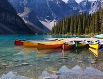 Morning light on canoes along the shore of Moraine Lake in Banff National Park. (Fotolia Image)