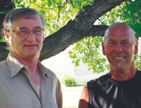 Following a discussion on bees, apiarist Don Kitson (left) and contractor Jim Hyrich both of Portage la Prairie, pause to have their picture taken in the shade beneath a magnificent old oak tree. (Photo by Ted Meseyton)