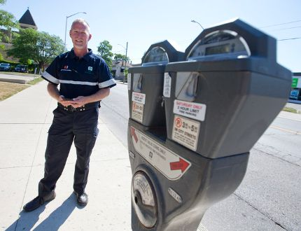 Parking Services Officer Scott Lambe wears his new uniform - navy blue pants and t-shirt with reflective safety stripes and an Android powered handheld device connected to a wireless printer - as he stands next to a Dundas Street parking meter in London. (CRAIG GLOVER, The London Free Press)