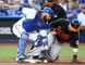 Russell Martin of the Toronto Blue Jays drops the ball while covering third base, allowing Manny Machado of the Baltimore Orioles to score at the Rogers Centre in Toronto, Ont. on Friday July 29, 2016. (Dave Abel/Toronto Sun/Postmedia Network)